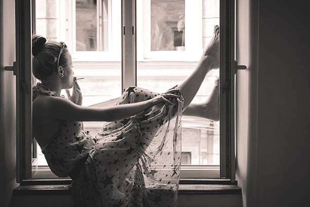 Young woman smoking and sitting on the window stock photo