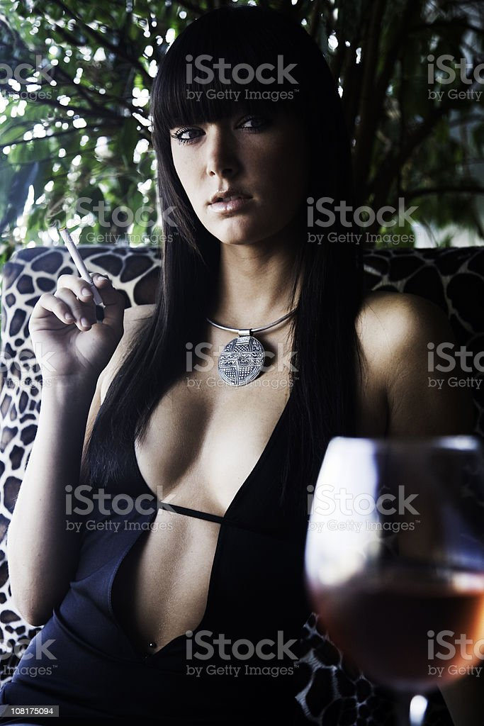 Young Woman Smoking Cigarette and Drinking Wine stock photo