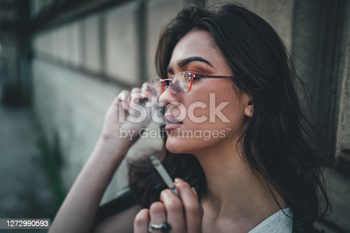 Portrait of young woman smoking cigarette outdoor