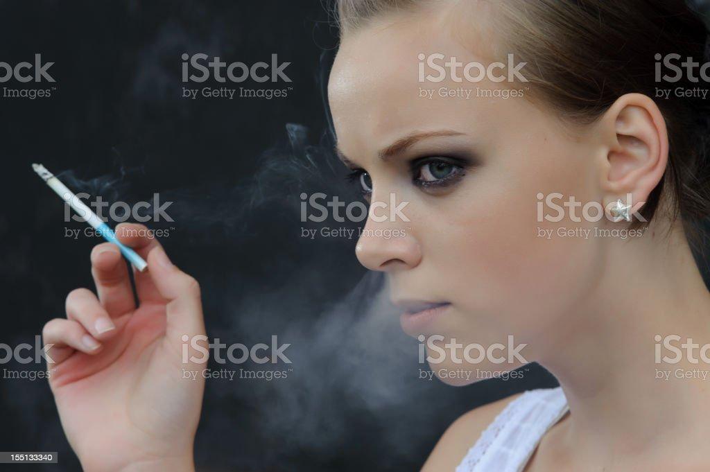Young woman smoking, cigarette smoke passing through her nose stock photo