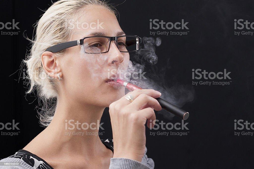Young woman smoking e-cigarette royalty-free stock photo