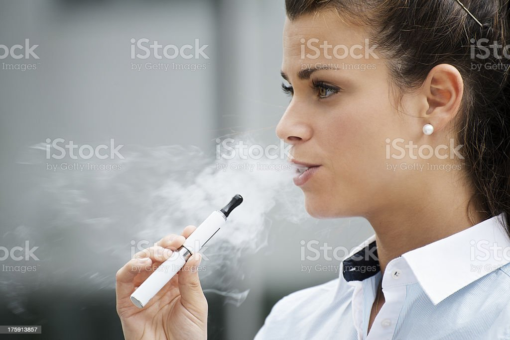 Joven mujer fumando cigarrillo electrónico al edificio de oficinas - Foto de stock de Cigarrillo electrónico libre de derechos