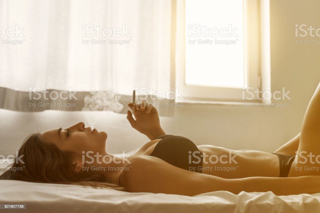 Young woman smoking in bedroom stock photo