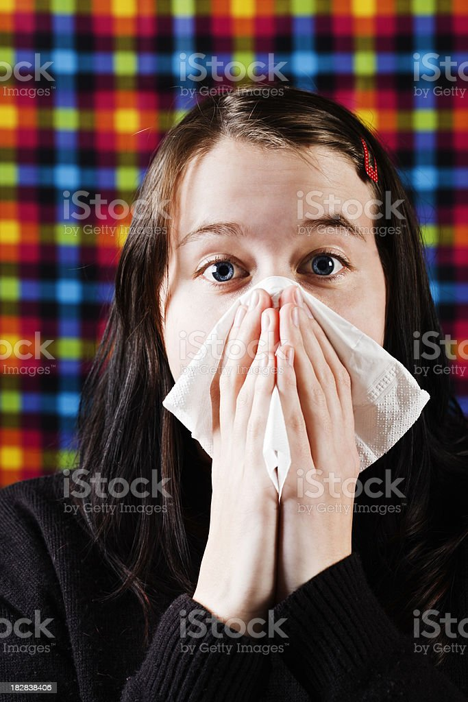 Young woman sneezes and blows her nose royalty-free stock photo
