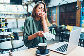 Young woman sneezing while working with laptop at cafe