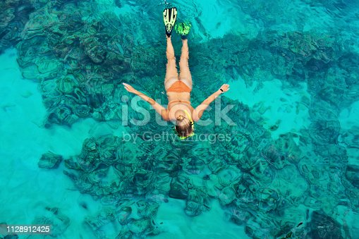 577645320 istock photo Young woman snorkeling with coral reef fishes 1128912425