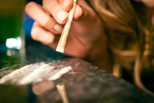 istock Young woman snorting cocaine with rolled up dollar 148489467