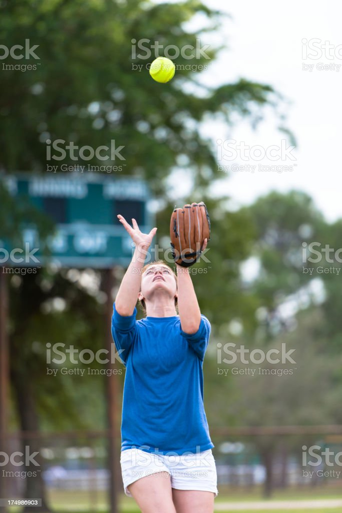 Young Woman Softball Player Running to Catch Ball stock photo