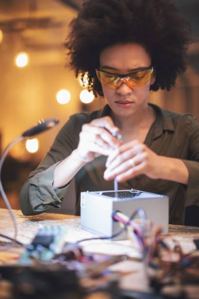 Junge Frau Löten von Leiterplatten in ihrem Tech-Büro – Foto