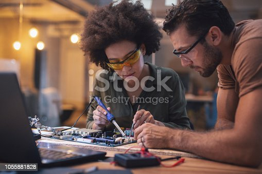 Woman Soldering a circuit board in her office. Shallow DOF. Developed from RAW; retouched with special care and attention; Small amount of grain added for best final impression.16 bit Adobe RGB color profile.
