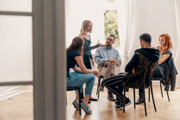 Young woman solving problems with friend during group therapy for teenagers Young woman solving problems with friend during group therapy for teenagers drug rehab stock pictures, royalty-free photos & images