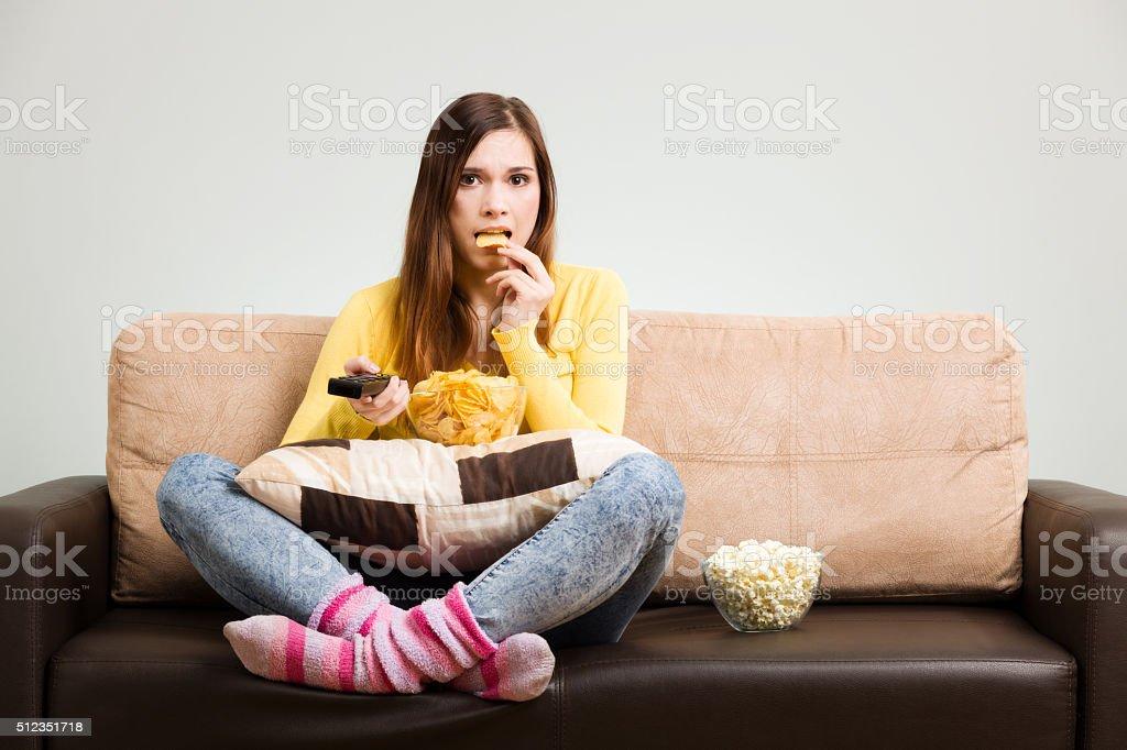 Mulher jovem passa seu tempo livre assistindo à TV - foto de acervo