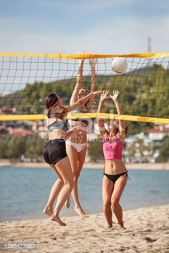Young woman in bikini playing beach volley with friends, spiking in the net