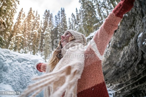 Young woman arms outstretched near frozen waterfall in canyon, Winter