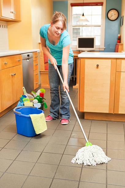 young woman spring cleaning mopping in the kitchen - commercial dishwasher stock photos and pictures