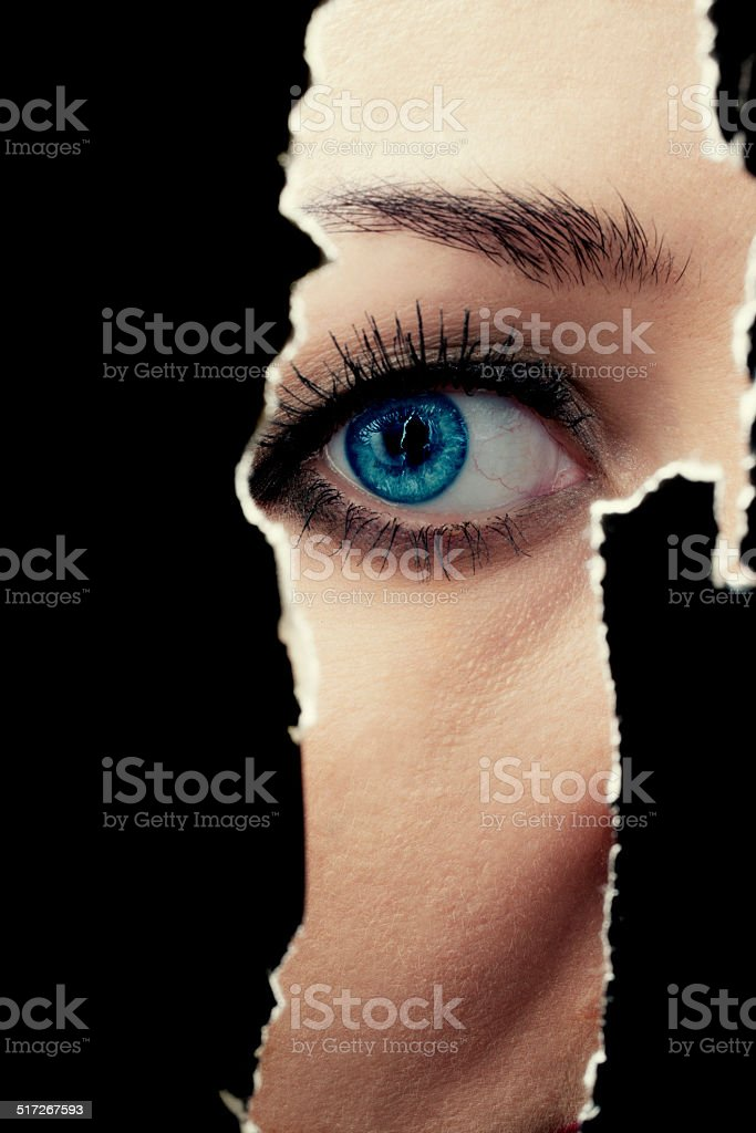 One eye of a young woman spying through a hole in the wall