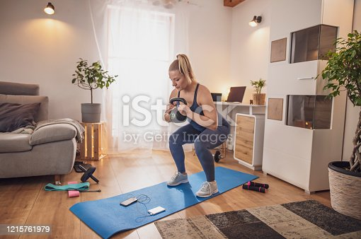 Young woman watching smart phone and squatting with kettlebell on yoga mat in living room