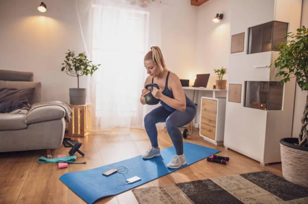 mujer joven en cuclillas con kettlebell en estera de yoga en la sala de estar - pesa rusa fotografías e imágenes de stock