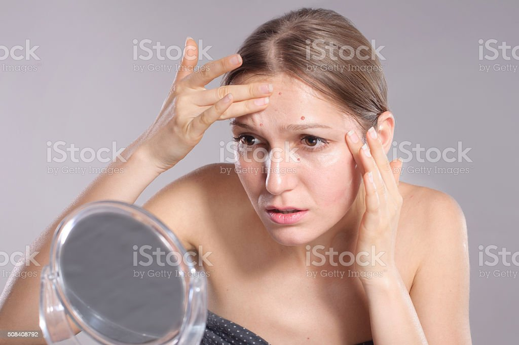 Young woman squeeze her acne in front of the mirror stock photo
