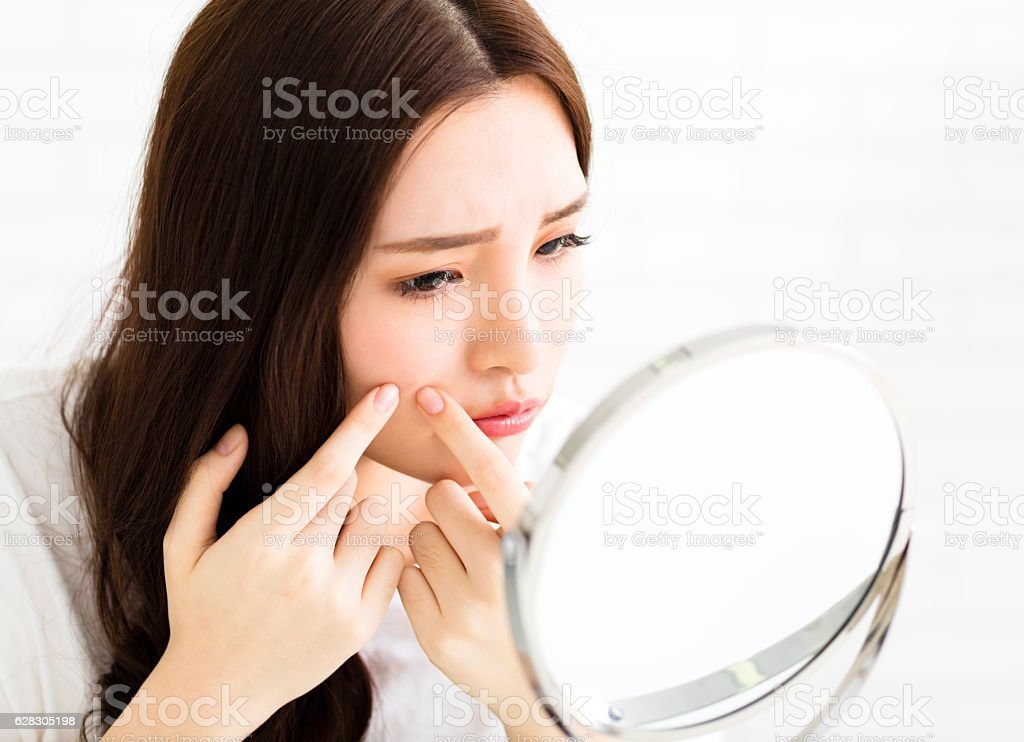 young woman squeeze her acne in front of the mirror - foto stock