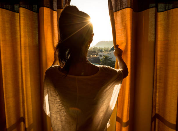 Young woman stand in the room open curtain seeing the beautiful sunrise stock photo