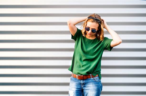 mujer joven de pie contra la pared. - moda playera fotografías e imágenes de stock