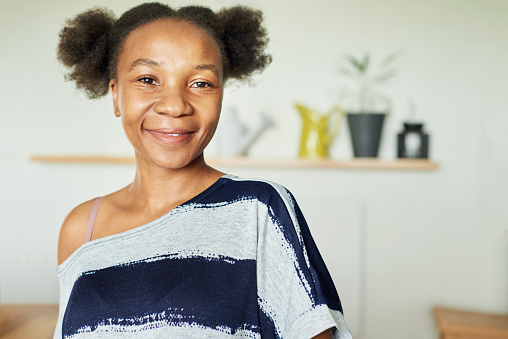 Portrait of a carefree young African woman smiling while standing alone at home in the afternoon