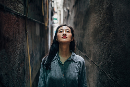 Young woman standing alone in alley