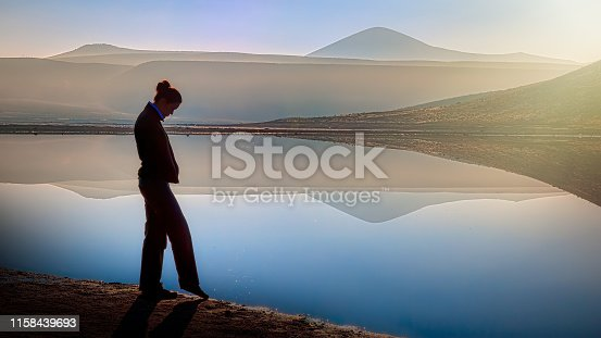 Young woman standing alone on edge of staring at lake and thinking. Mist over water.