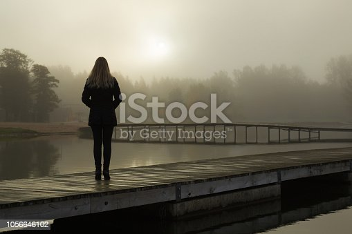Young woman standing alone on lake footbridge and staring at sunrise in gray, cloudy sky. Mist over water. Foggy air. Early chilly morning. Dark, scary moment and gloomy atmosphere. Back view.