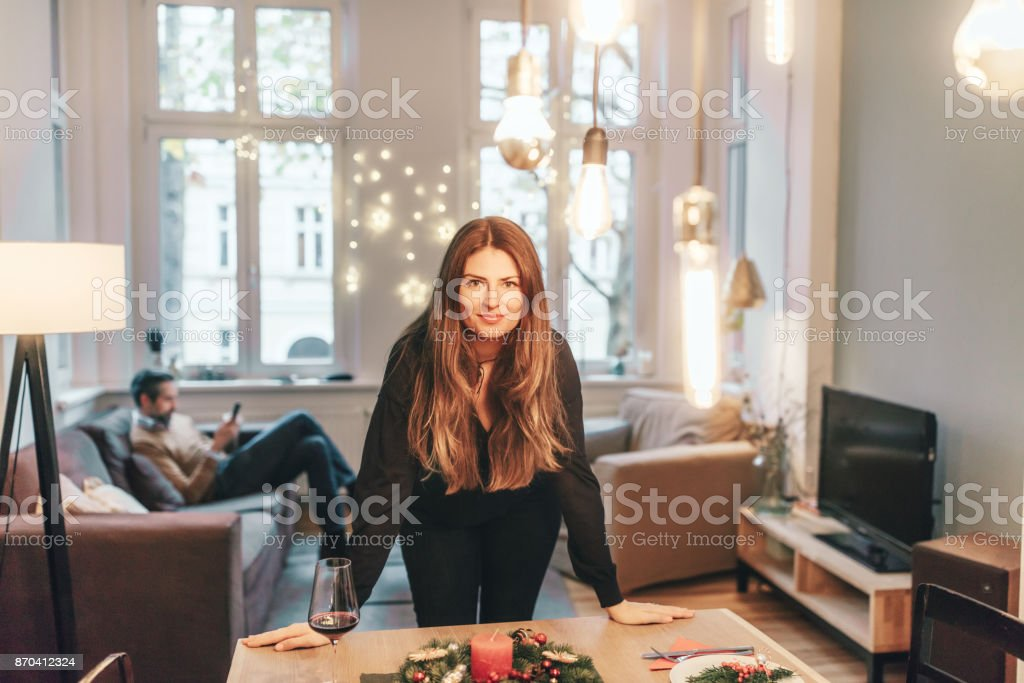 young woman standing at dining table with christmas decoration – zdjęcie