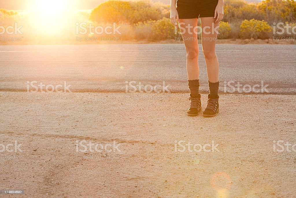 Young woman standing at roadside, low section royalty-free stock photo