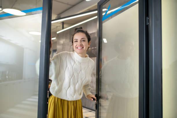 Junge Frau steht vor der Tür und lächelt glücklich – Foto