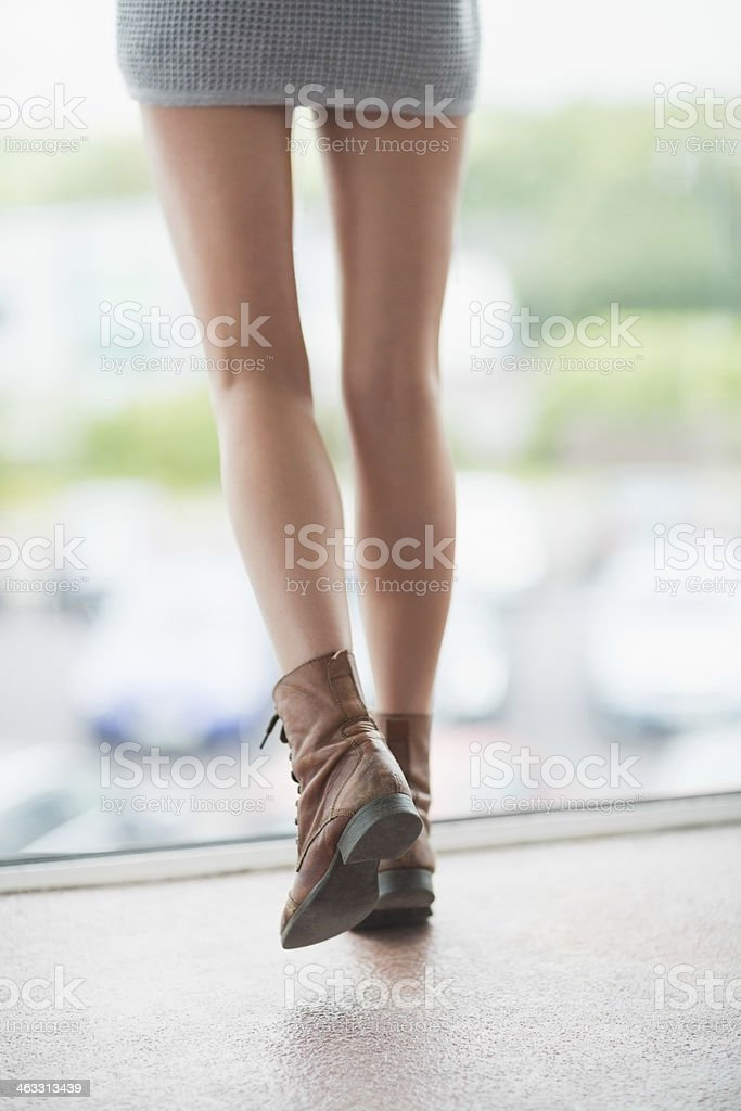 Young woman standing at the window stock photo