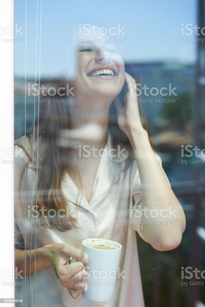 Junge Frau, die hinter Glas der Balkontür – Foto