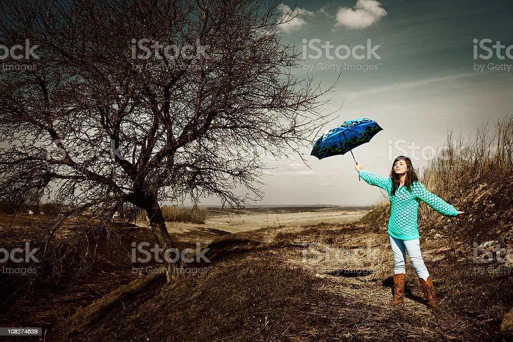 Young Woman Standing Beside Tree Holding Blue Umbrella royalty-free stock photo