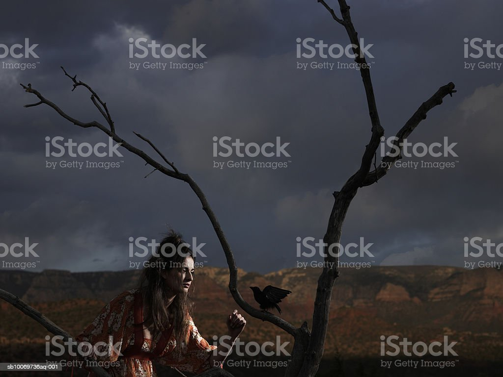 Young woman standing besides tree at dusk royalty-free stock photo