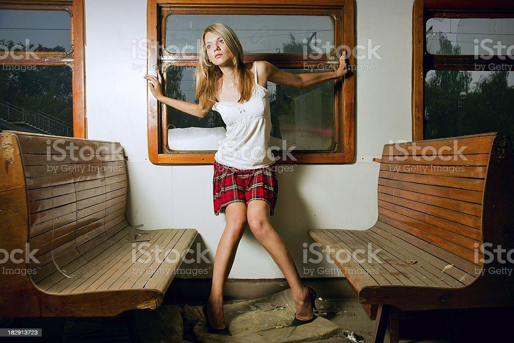Молодая женщина, стоя между скамьи в поезд автомобилей стоковое фото