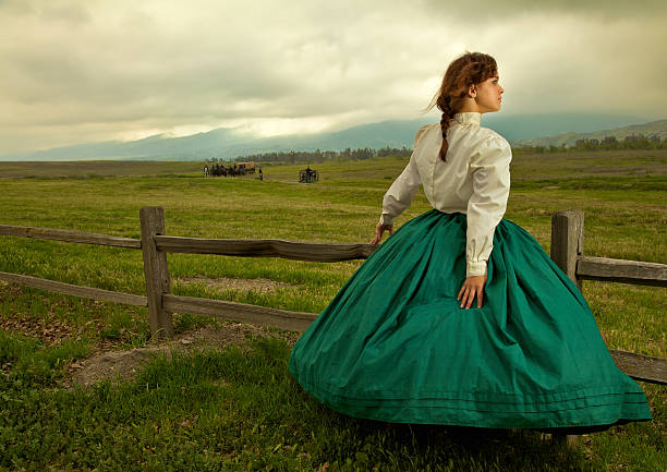 young woman standing by a field during the civil war - civil war stock photos and pictures