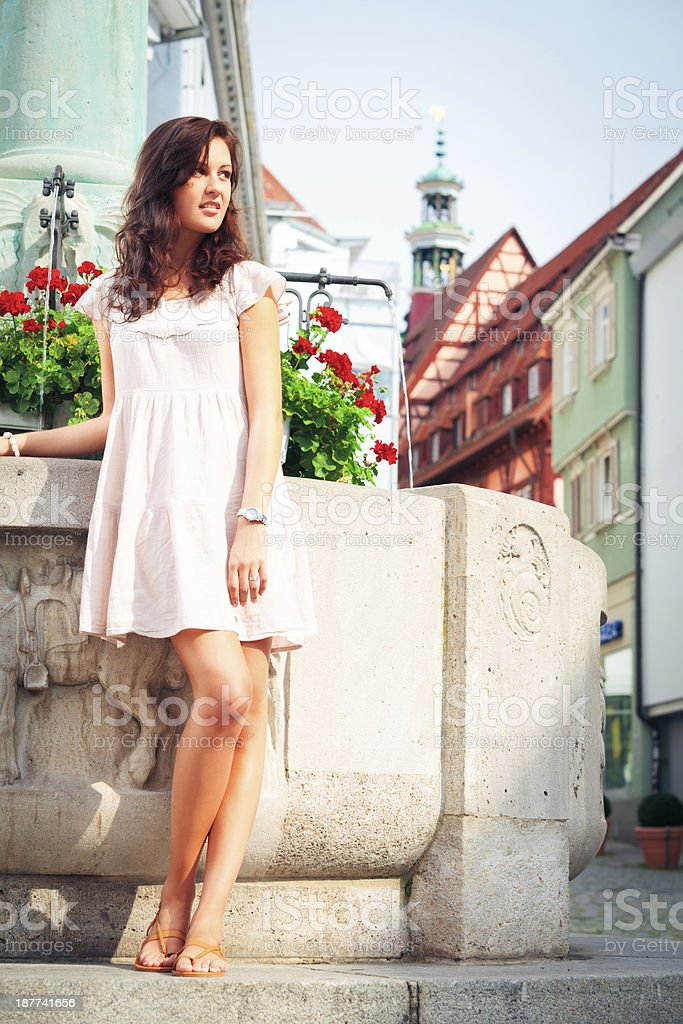 young woman standing by a fountain stock photo