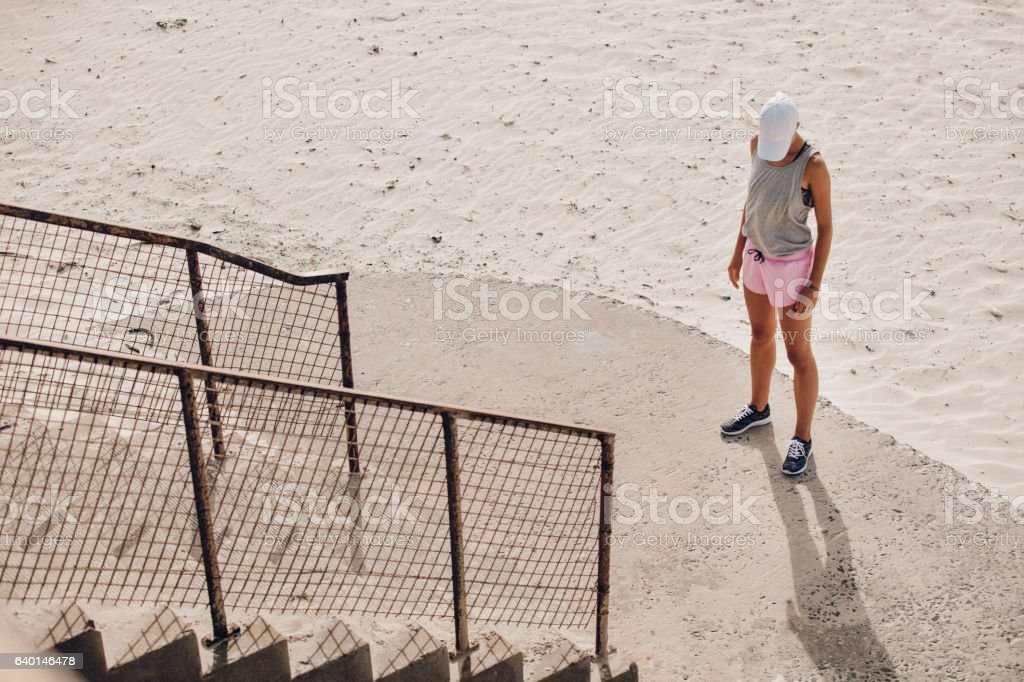 Young woman standing by a staircase at the beach stock photo