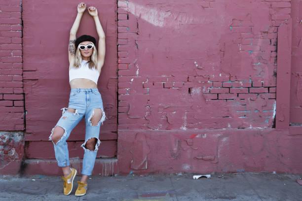 junge Frau steht an einer Wand mit Sonnenbrille und schwarzem Hut – Foto