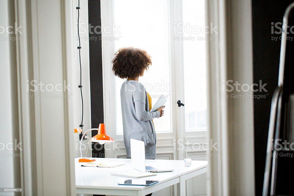 Young woman standing by a window in office stock photo