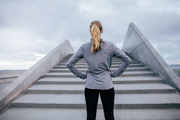 Young woman standing by steps outdoors Rear view shot of young woman standing by steps outdoors with her hands on hips. Fitness woman before workout. akimbo stock pictures, royalty-free photos & images