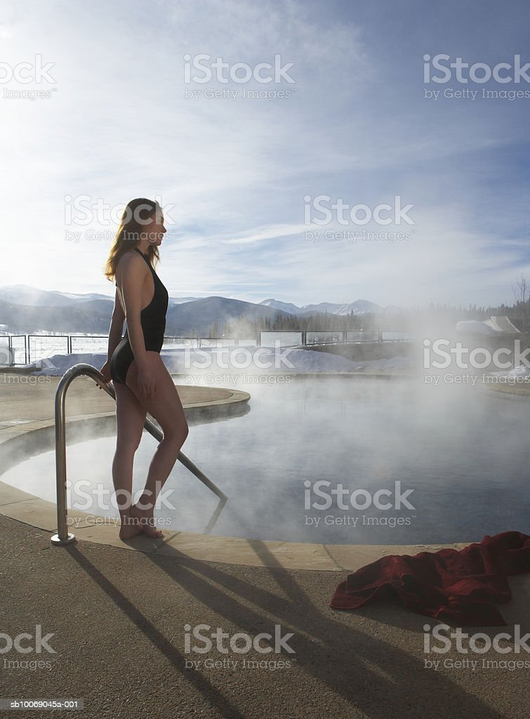 Young woman standing by swimming pool 免版稅 stock photo