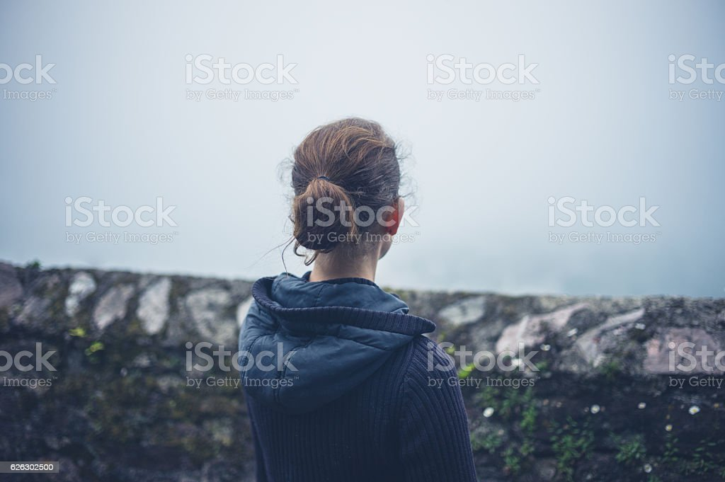 Young woman standing by wall in fog stock photo