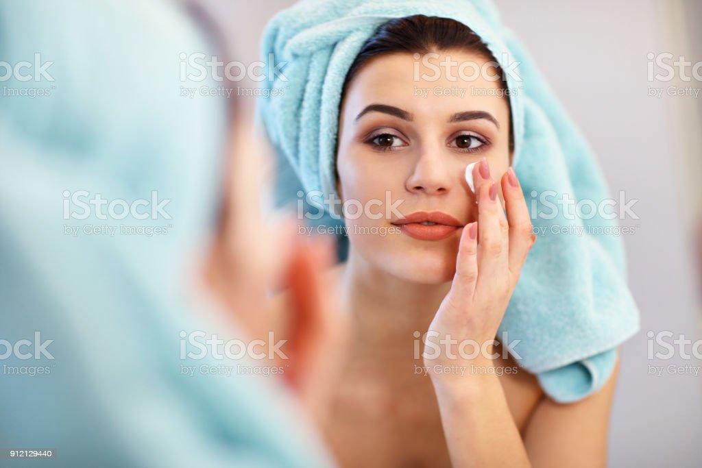 Junge Frau steht im Badezimmer und Gesichtscreme morgens anwenden – Foto