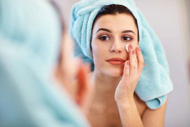 若い女性の浴室に立って、朝の顔のクリームを適用します。 ストックフォト