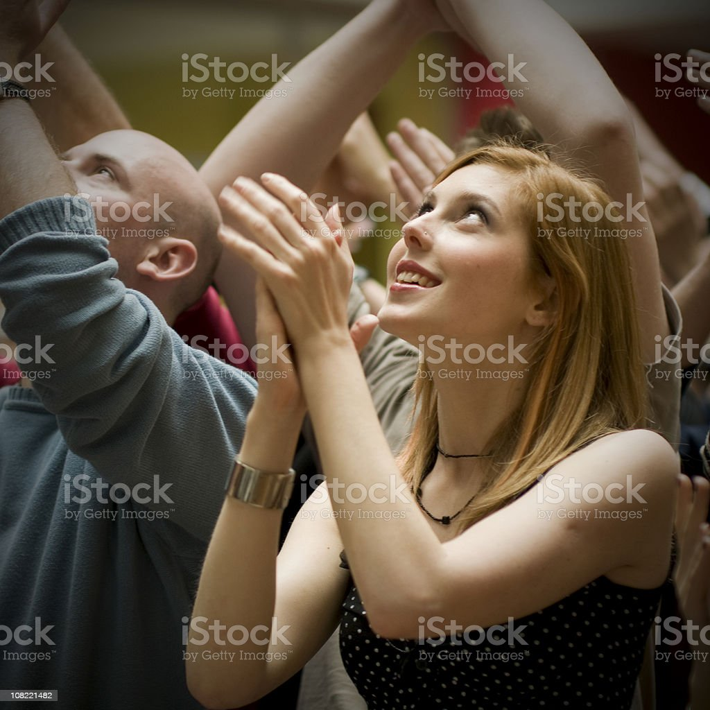 Young Woman Standing in Crowd and Clapping royalty-free stock photo