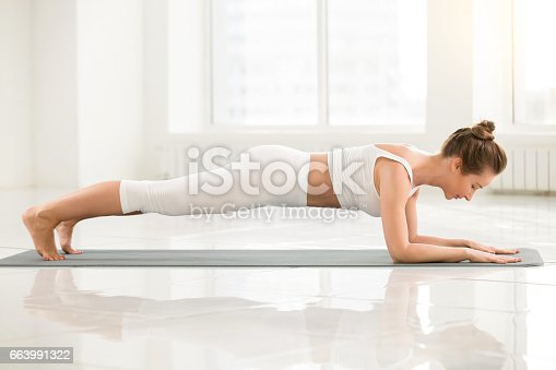 istock Young woman standing in Dolphin Plank pose, white color backgrou 663991322